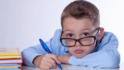 A young boy with eyeglasses and pen in his hand