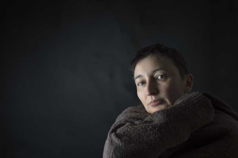 emotions of divorce: depressed woman with head on knees against a black background