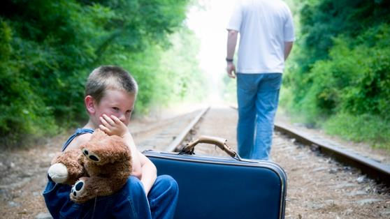 a man walking away from a child sitting on a track