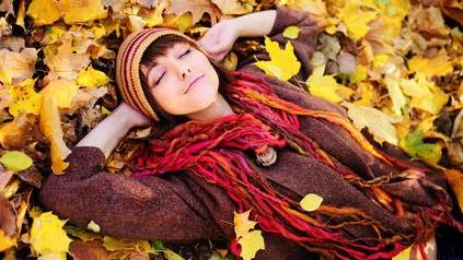 a girl resting on ground strewn with leaves