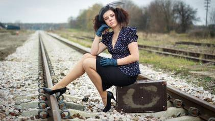 a woman sitting on a train track