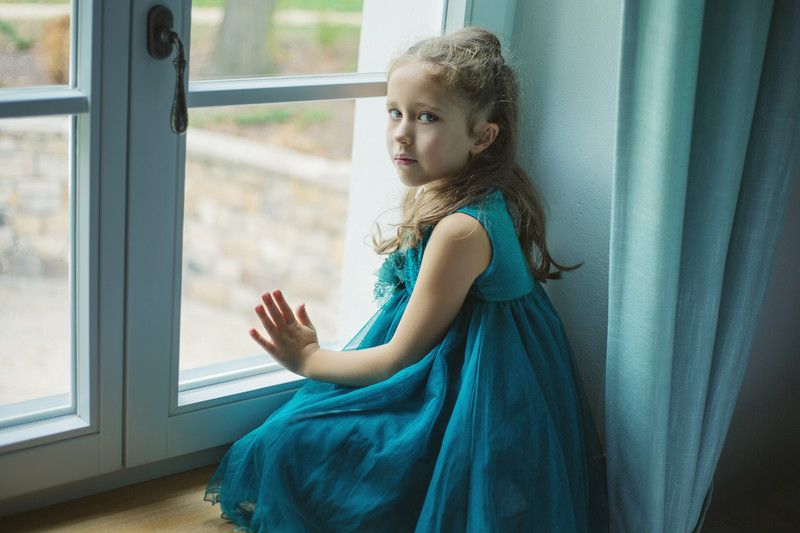 parental alienation: Sad young girl in blue dress looking out the window