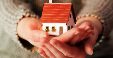 what you need to know about mortgages: woman's hands holding a model home