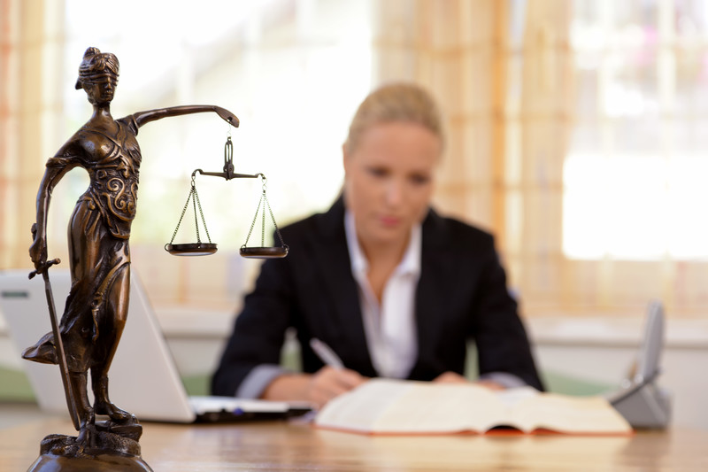 divorce lawyer: woman in suite sitting at her desk looking over paperwork