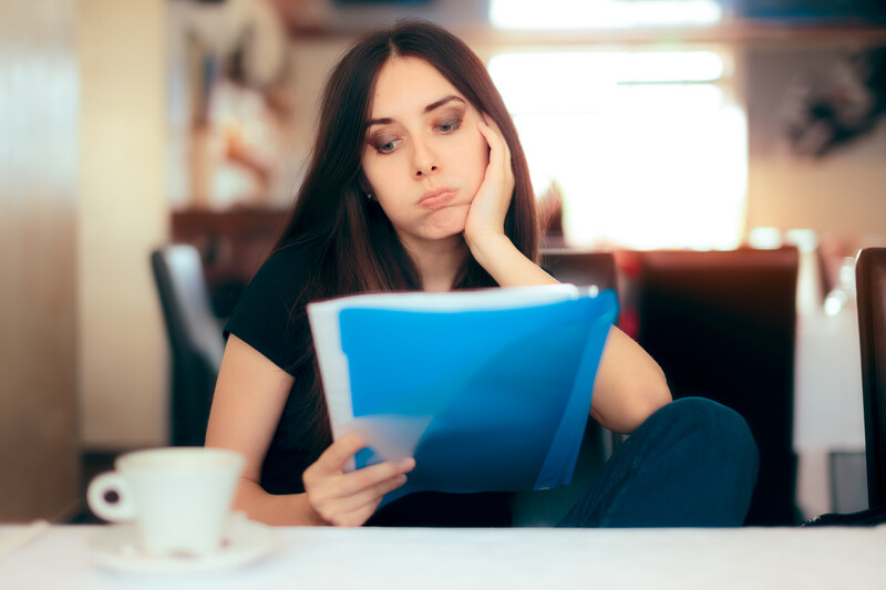divorce preparaton: exasperated woman looking at some paperwork