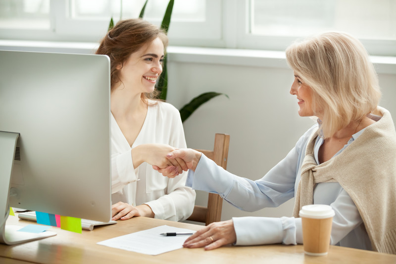 good divorce attorney: female lawyer shaking hands and smiliing with a divorcing mother