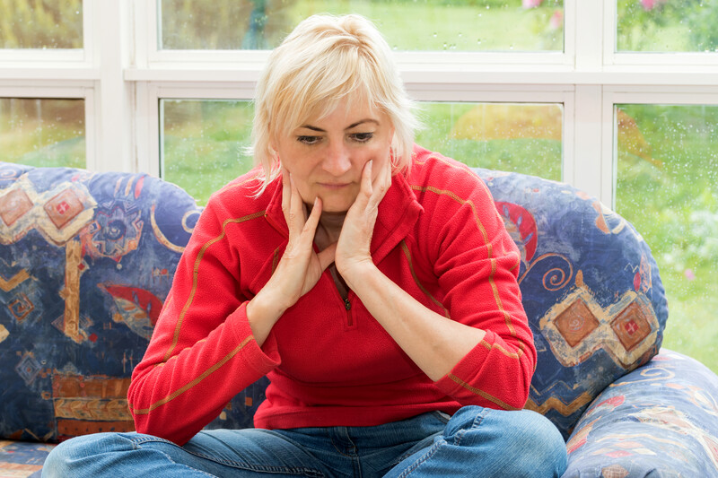post-traumatic stress after divorce: depressed blonde woman sitting on red couch