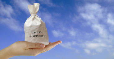 state child support guidelines: female hand hold a bag of money marked child support