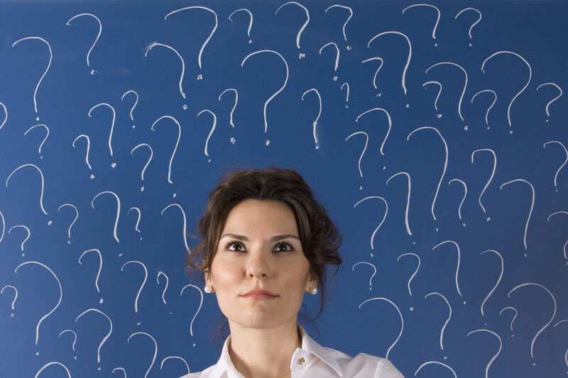 thinking about divorce: woman in front of blue background surrounded by question marks
