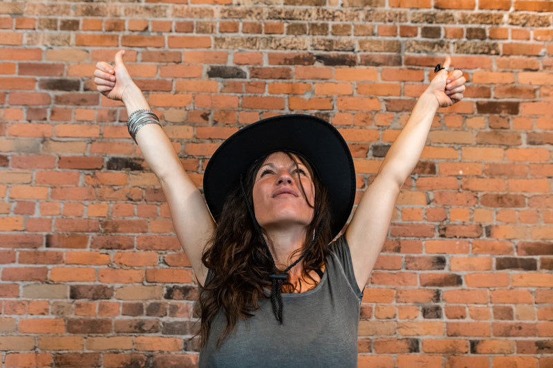 fearless after divorce: empowered woman with arms over head in front of brick wall