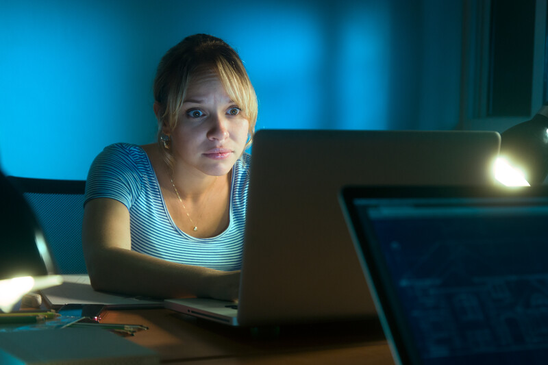 social media and single moms: woman in the glow of her computer looking at social media