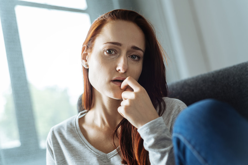 thinking about divorce: sad red headed woman on couch thinking