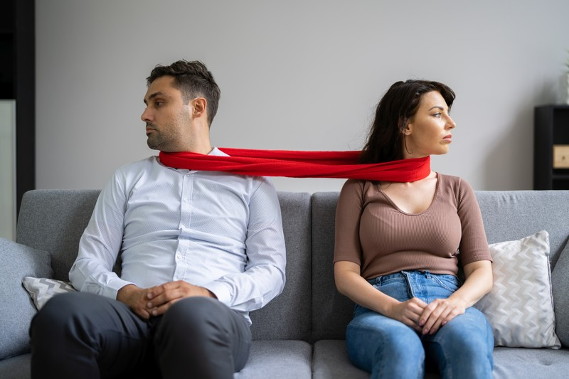 divorce if you were codependent: man and woman sitting on a couch tied together with a red scarf