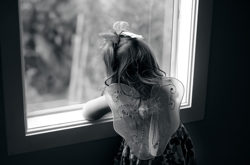 ex checks-out: sad little girl in angel wings looking out the window for daddy