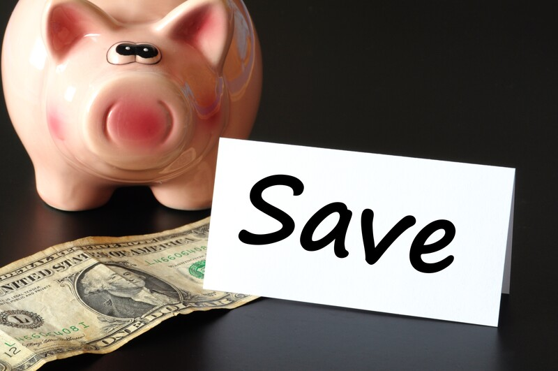 save money during divorce: pink piggy bank with dollar bill laying next to it.