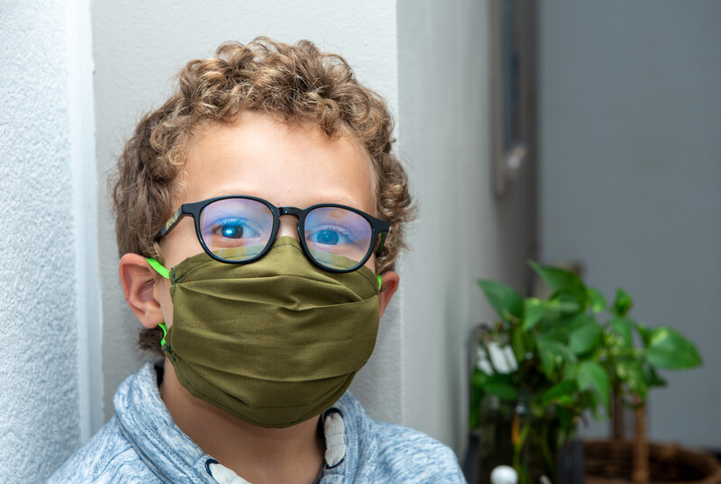 masking your children: curly haired boy with covid mask on