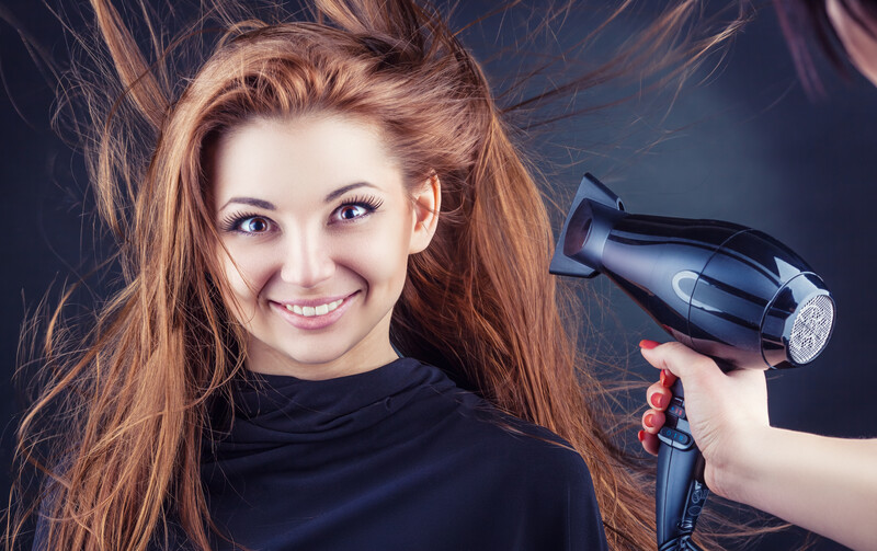 red headed woman with hair being blown dry